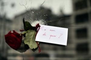 """""""In nome di chi?"""", chiede il biglietto che accompagna la rosa in un foro di proiettile del  Bataclan."""