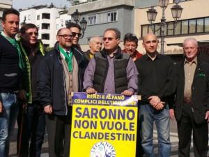 Il presidio della Lega di Saronno contro l'accoglienza dei profughi, con il sindaco Fagioli in prima fila e uno dei manifesti affissi in città.